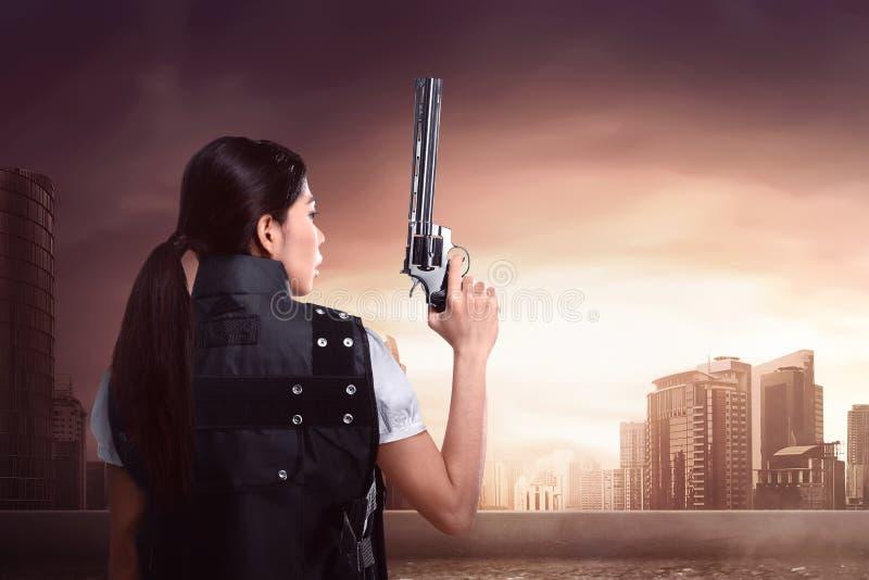 Πίσω άποψη της προκλητικής ασιατικής γυναίκας που χρησιμοποιεί την αστυνομία ομοιόμορφη με το πυροβόλο όπλο στοκ φωτογραφία με δικαίωμα ελεύθερης χρήσης