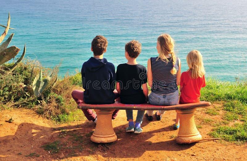 Πίσω άποψη της τετραμελούς οικογένειας που κάθεται στην παραλία στοκ εικόνες με δικαίωμα ελεύθερης χρήσης
