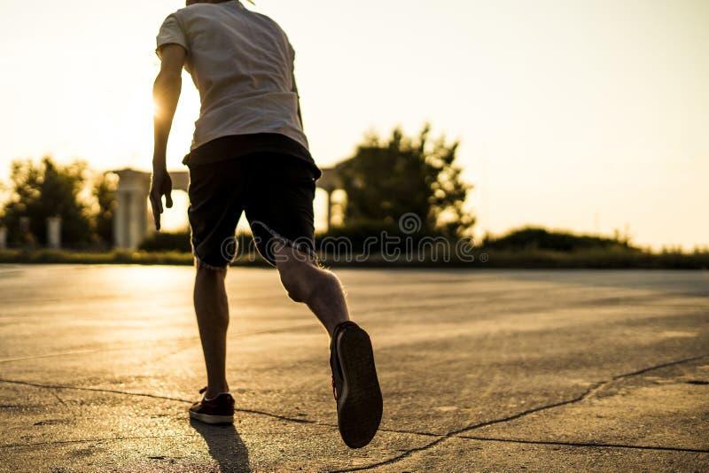 Πίσω άποψη του αθλητή νεαρών άνδρων στην περιστασιακή σκιαγραφία που τρέχει στην αστική πόλη σε ένα ηλιοβασίλεμα στοκ φωτογραφίες