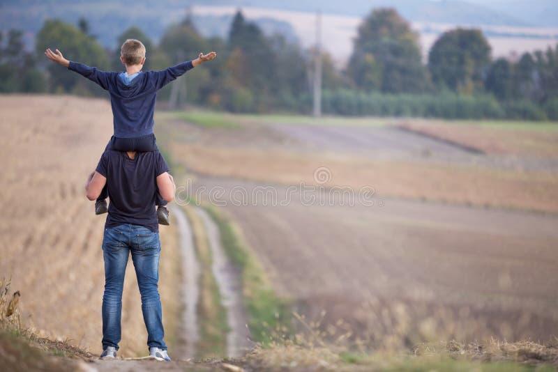 Πίσω άποψη του αθλητικού πατέρα που συνεχίζει το περπάτημα γιων ώμων μέσω του χλοώδους τομέα στα θολωμένους ομιχλώδεις πράσινους  στοκ εικόνες