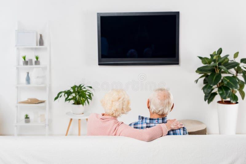 πίσω άποψη του ανώτερου ζεύγους που προσέχει τη TV και το αγκάλιασμα στοκ εικόνα