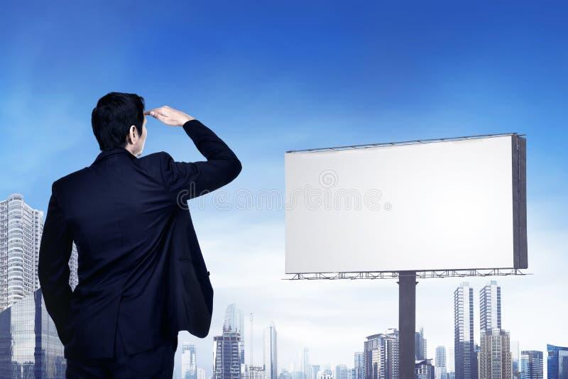 Πίσω άποψη του ασιατικού επιχειρηματία που εξετάζει τον κενό πίνακα διαφημίσεων FO στοκ εικόνες με δικαίωμα ελεύθερης χρήσης