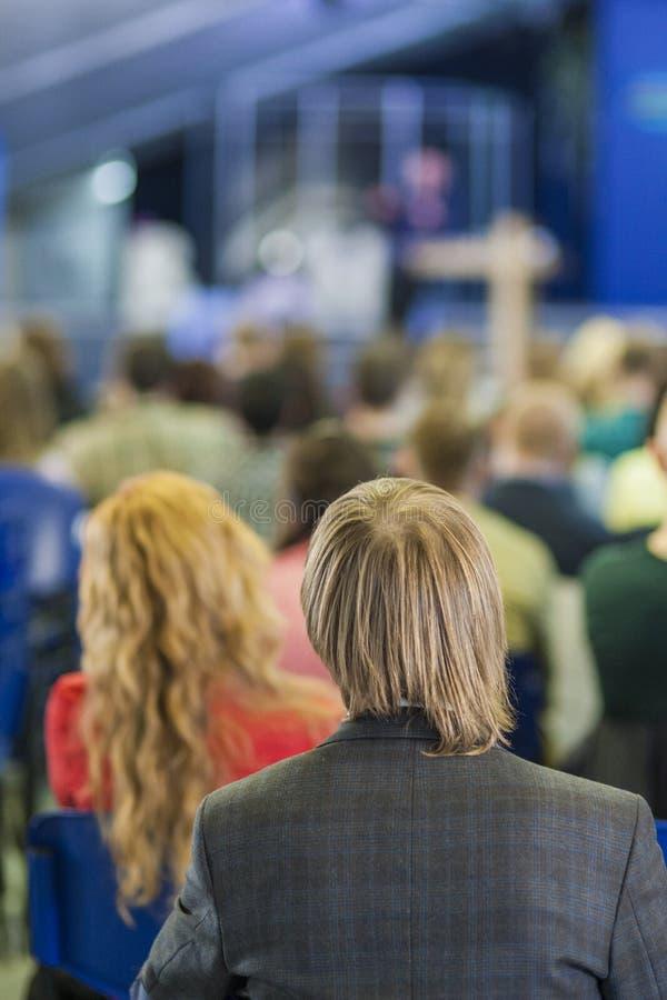Πίσω άποψη του ατόμου που ακούει την επαγγελματική ομιλία ομιλητών μπροστά από τους ανθρώπους στοκ φωτογραφίες με δικαίωμα ελεύθερης χρήσης