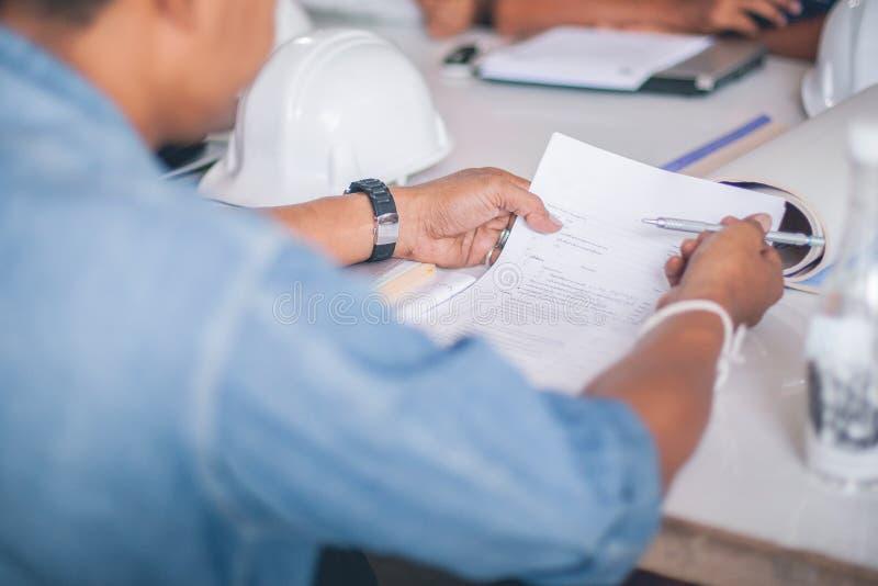Πίσω άποψη του εγγράφου ανάγνωσης εργατών οικοδομών στοκ εικόνες με δικαίωμα ελεύθερης χρήσης