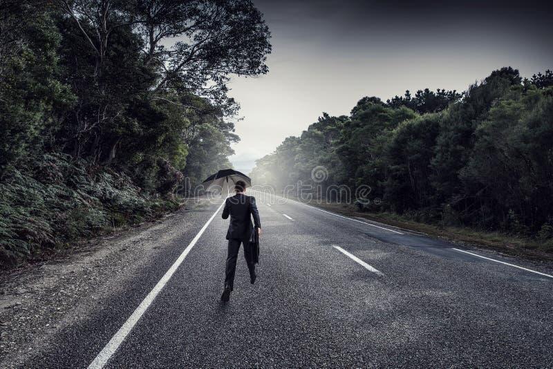 Πίσω άποψη του επιχειρηματία με την ομπρέλα και της βαλίτσας που περπατά στο δρόμο Μικτά μέσα στοκ φωτογραφία με δικαίωμα ελεύθερης χρήσης