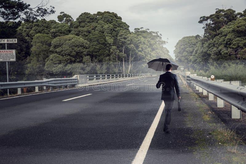 Πίσω άποψη του επιχειρηματία με την ομπρέλα και της βαλίτσας που περπατά στο δρόμο Μικτά μέσα στοκ φωτογραφία