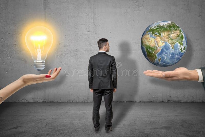Πίσω άποψη του επιχειρηματία που στέκεται μεταξύ δύο μεγάλων χεριών, χέρι της γυναίκας που lightbulb, ανθρώπινο χέρι που λίγα στοκ εικόνες με δικαίωμα ελεύθερης χρήσης