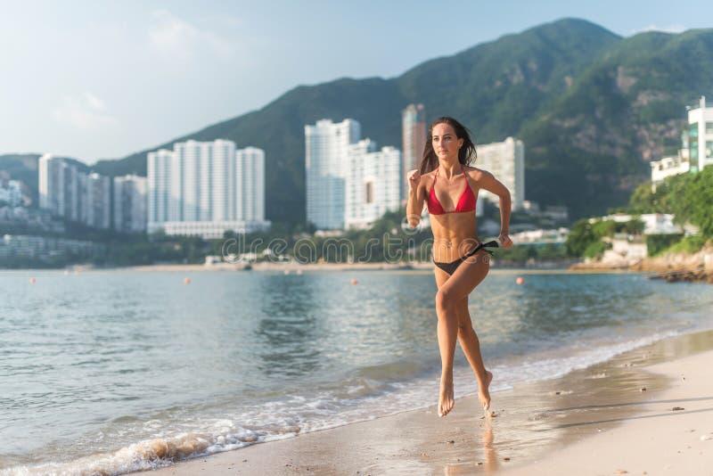 Πίσω άποψη του κατάλληλου λεπτού τρεξίματος κοριτσιών χωρίς παπούτσια στην ακτή που φορά το μπικίνι Νέα γυναίκα που κάνει την καρ στοκ εικόνα