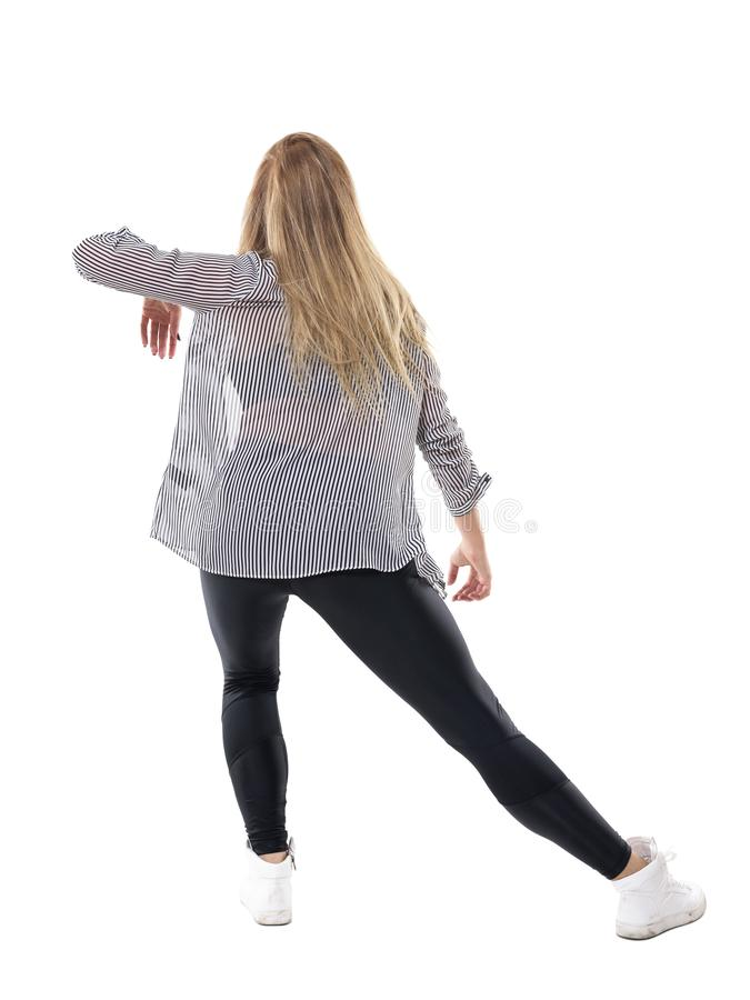 Πίσω άποψη του κομψού χαριτωμένου μακρυμάλλους ξανθού χορού γυναικών αργά στο ρυθμό μουσικής στοκ εικόνα με δικαίωμα ελεύθερης χρήσης