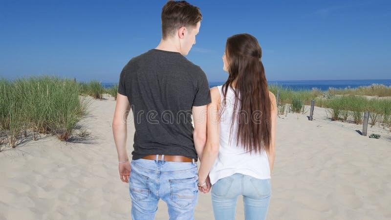 Πίσω άποψη του νέου ζεύγους στην άμμο και τον ωκεανό παραλιών αμμόλοφων στοκ φωτογραφία με δικαίωμα ελεύθερης χρήσης