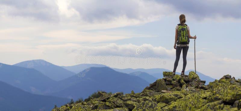 Πίσω άποψη του νέου λεπτού κοριτσιού τουριστών backpacker με το ραβδί που στέκεται στη δύσκολη κορυφή ενάντια στο φωτεινό μπλε ου στοκ φωτογραφία με δικαίωμα ελεύθερης χρήσης