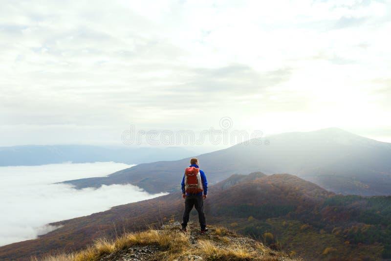 Πίσω άποψη του νέου οδοιπόρου τουριστών με το σακίδιο πλάτης που στέκεται στην κορυφή του βουνού και που εξετάζει όμορφο κίτρινο στοκ εικόνα