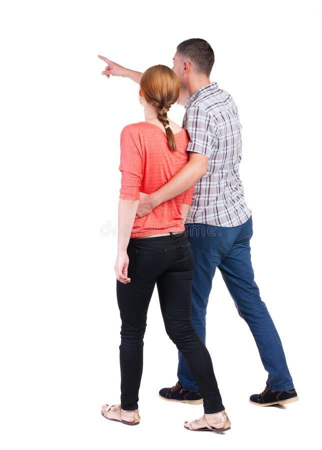 Πίσω άποψη του περπατώντας νέου ζεύγους (άνδρας και γυναίκα) που δείχνει στοκ φωτογραφίες