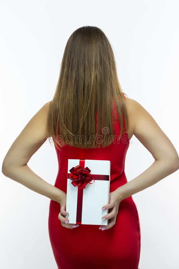 Πίσω άποψη του προκλητικού καυκάσιου θηλυκού στην κόκκινη εκμετάλλευση άσπρο Giftbox φορεμάτων με την κόκκινη κορδέλλα πίσω από τ στοκ φωτογραφία με δικαίωμα ελεύθερης χρήσης