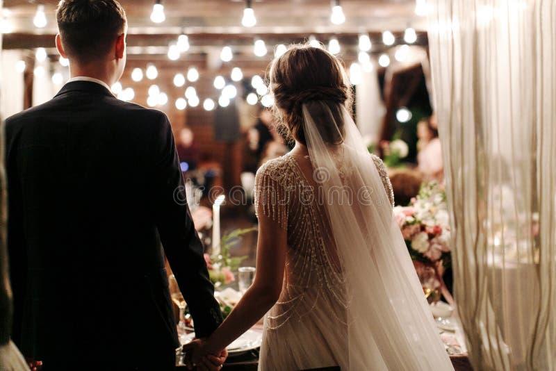 Πίσω άποψη του ρομαντικού ζεύγους της νύφης και του νεόνυμφου στο συμπόσιο χέρι-χέρι Τα φω'τα της ηλεκτρικής γιρλάντας φωτίζουν τ στοκ εικόνες με δικαίωμα ελεύθερης χρήσης