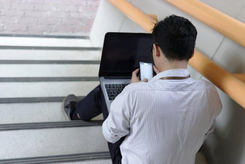 Πίσω άποψη του τονισμένου νέου ασιατικού επιχειρησιακού ατόμου που κάθεται και που χρησιμοποιεί το κινητά έξυπνα τηλέφωνο και το  στοκ φωτογραφία με δικαίωμα ελεύθερης χρήσης