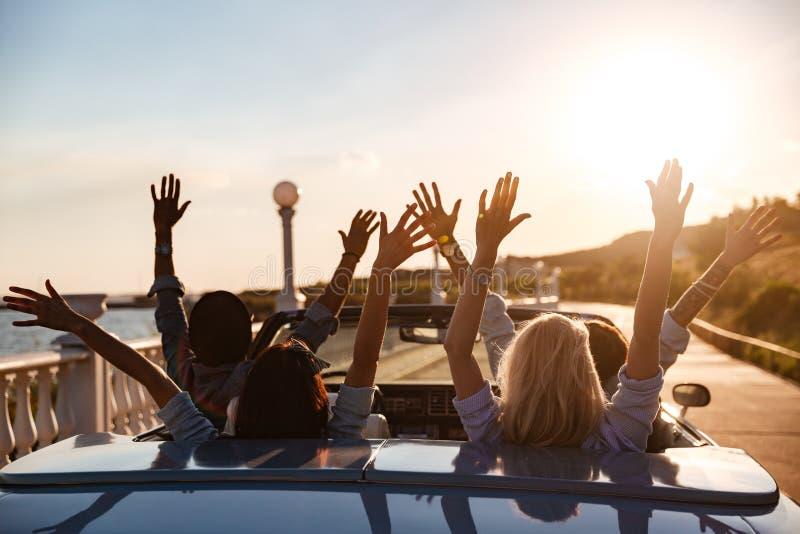Πίσω άποψη των ευτυχών φίλων που οδηγούν το καμπριολέ με τα αυξημένα χέρια στοκ εικόνες με δικαίωμα ελεύθερης χρήσης