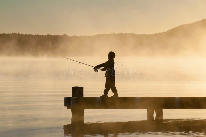 Πίσω αναμμένο αγόρι που αλιεύει από έναν λιμενοβραχίονα στοκ φωτογραφία