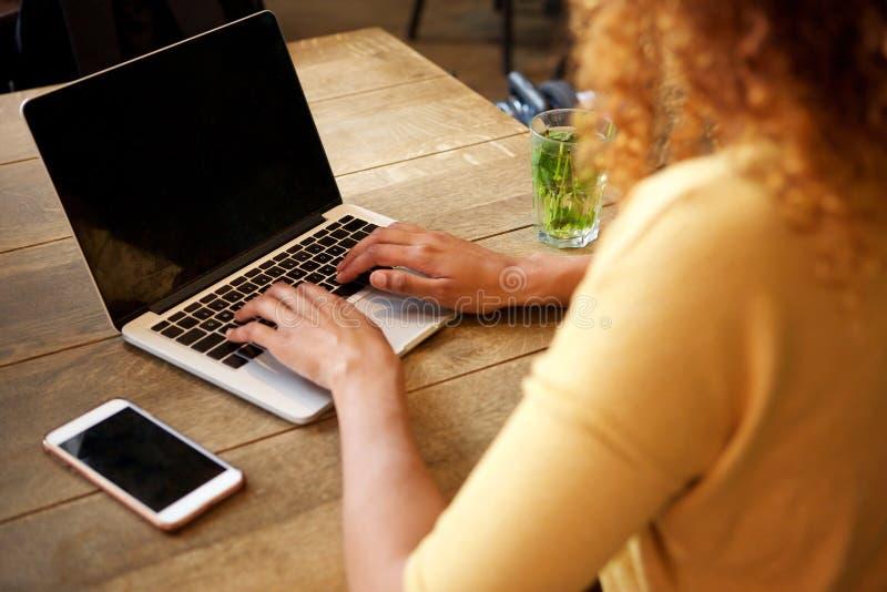 Πίσω από της νέας γυναίκας που χρησιμοποιεί το φορητό προσωπικό υπολογιστή στοκ εικόνα με δικαίωμα ελεύθερης χρήσης