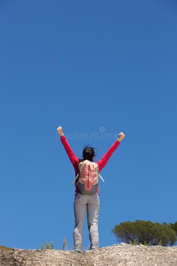Πίσω από το θηλυκό οδοιπόρο που στέκεται υπαίθρια με τα χέρια που αυξάνονται στοκ φωτογραφία