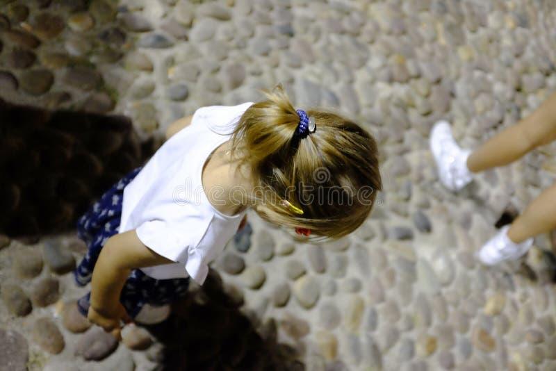 Πίσω ενός ατόμου σε ένα άσπρο πουκάμισο Στο υπόβαθρο ένα κορίτσι παίζει το βιολί στα φω'τα νύχτας στοκ εικόνα