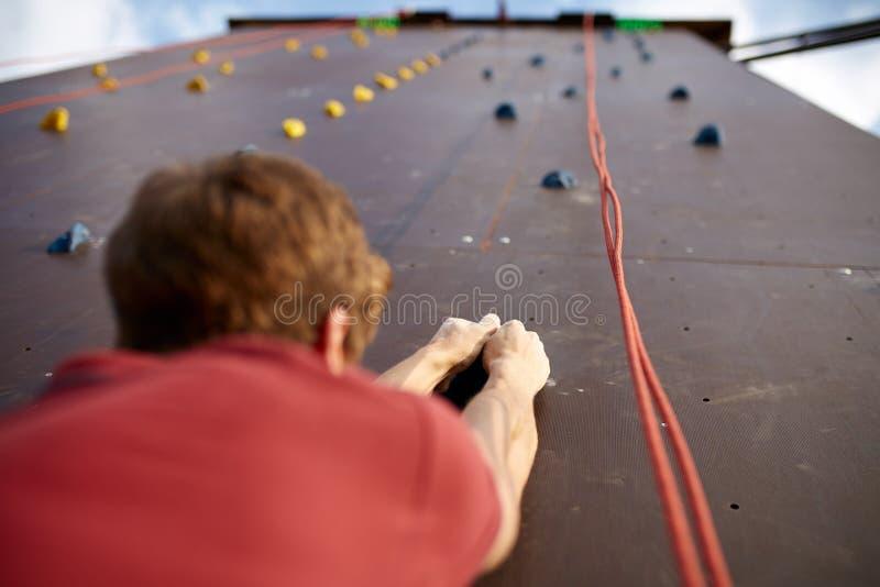 Πίσω κινηματογράφηση σε πρώτο πλάνο άποψης των χεριών ορειβατών σε έναν γάντζο βράχου του τεχνητού τοίχου αναρρίχησης υπαίθρια Νέ στοκ εικόνες με δικαίωμα ελεύθερης χρήσης