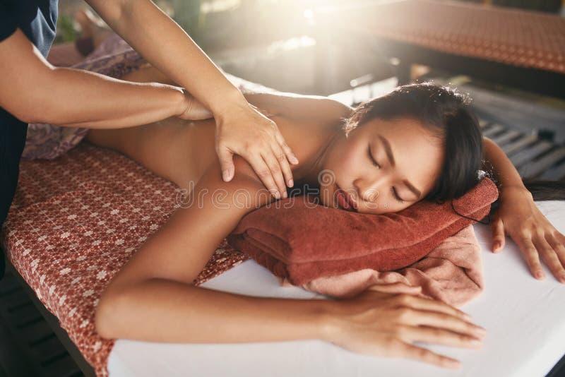 Πίσω μασάζ στην ταϊλανδική SPA Γυναίκα που έχει το μασάζ σώματος στο σαλόνι στοκ εικόνες
