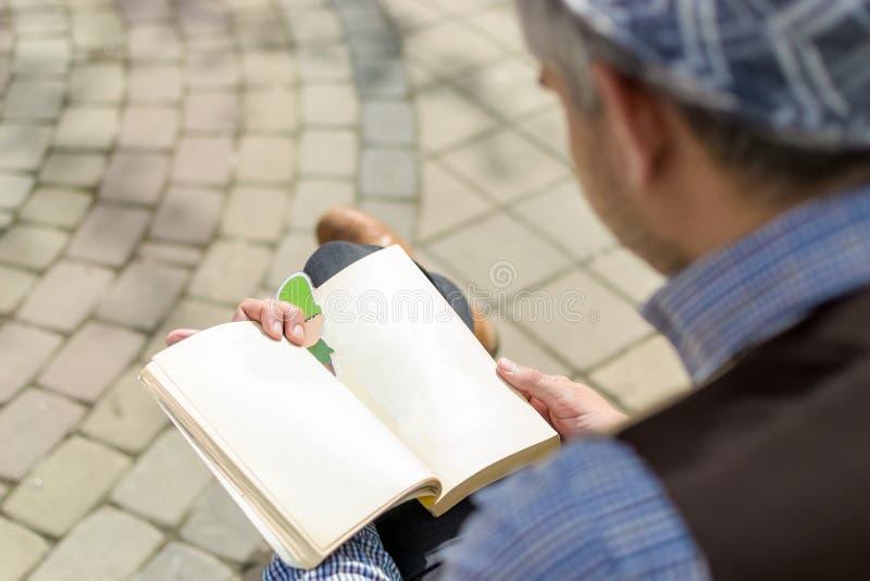 Πίσω πέρα από τον ώμο του για να δει τι το άτομο στα πόδια συνεδρίασης καπέλων διέσχισε και ανάγνωση ένα βιβλίο στοκ εικόνες