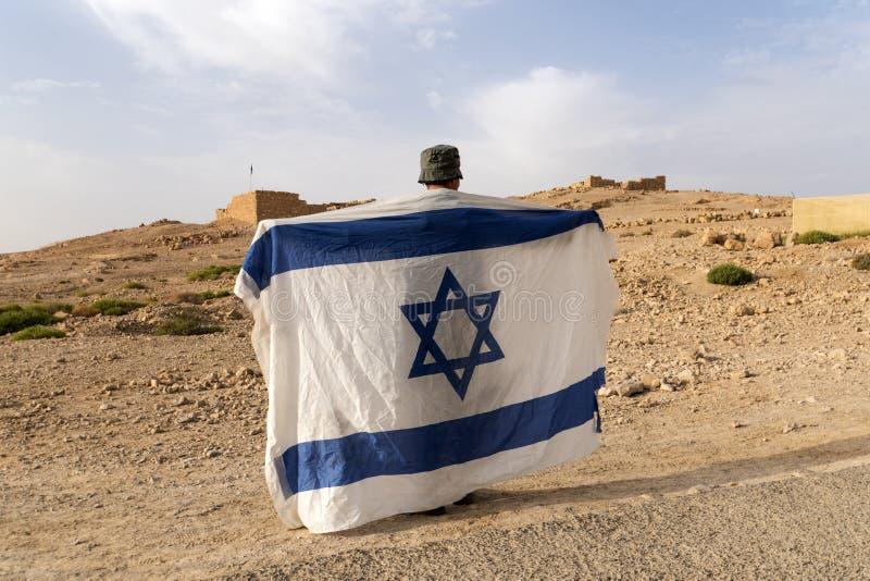 Πίσω πλευρά ενός στρατιώτη στο καπέλο που κρατά τη εθνική σημαία του Ισραήλ - λευκό με τα μπλε λωρίδες και το αστέρι του Δαβίδ σε στοκ φωτογραφίες