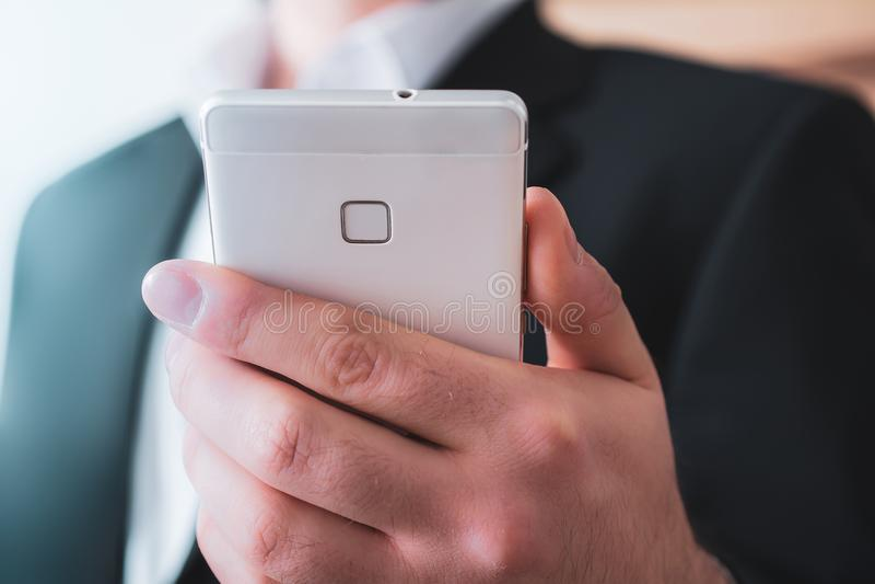 Πίσω πλευρά ενός Smartphone, Holded από το χέρι ενός επιχειρηματία στο κοστούμι στοκ εικόνα