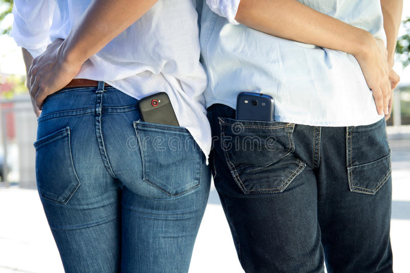Πίσω πορτρέτο του νέου ζεύγους με κινητό στην τσέπη στοκ φωτογραφίες