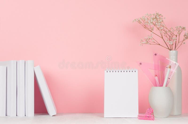 Πίσω στα σχολικά υπόβαθρα για το κορίτσι - άσπρα και ρόδινα χαρτικά, βιβλία, κενό σημειωματάριο στον άσπρο ξύλινο πίνακα και ρόδι στοκ φωτογραφία