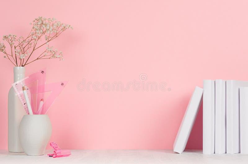Πίσω στα σχολικά υπόβαθρα για το κορίτσι - άσπρα και ρόδινα χαρτικά, βιβλία στον άσπρο ξύλινο πίνακα και το ρόδινο τοίχο στοκ εικόνες