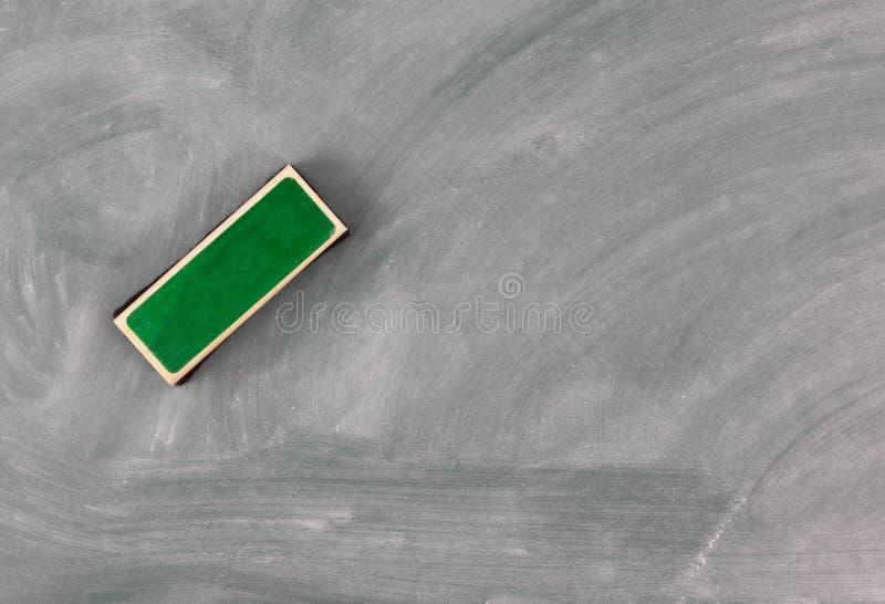 Πίσω στη σχολική έννοια με τον πράσινο πίνακα κιμωλίας συν τη γόμα στοκ φωτογραφία