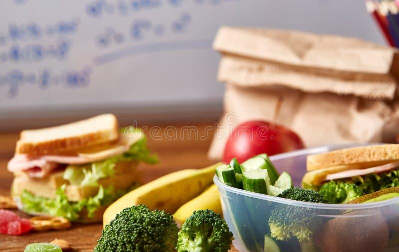 Πίσω στη σχολική έννοια, τις σχολικές προμήθειες, τα μπισκότα, το συσκευασμένα μεσημεριανό γεύμα και το καλαθάκι με φαγητό πέρα α στοκ φωτογραφία με δικαίωμα ελεύθερης χρήσης