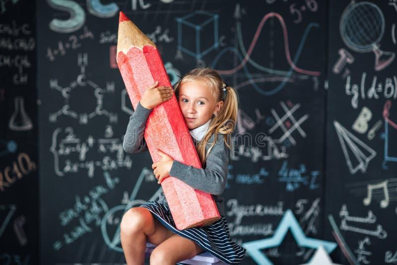 Πίσω στο σχολείο! Ένα μικρό κορίτσι κάθεται με το πολύ μεγάλο κόκκινο μολύβι στα χέρια της στο σχολείο ενάντια στον πίνακα κιμωλί στοκ φωτογραφία