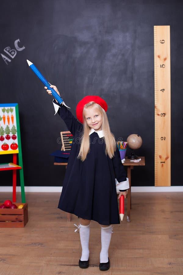 Πίσω στο σχολείο! Ένα μικρό κορίτσι στέκεται με τα μεγάλα μολύβια στα χέρια της στο σχολείο Το σχολικό κορίτσι αποκρίνεται στο μά στοκ εικόνα με δικαίωμα ελεύθερης χρήσης