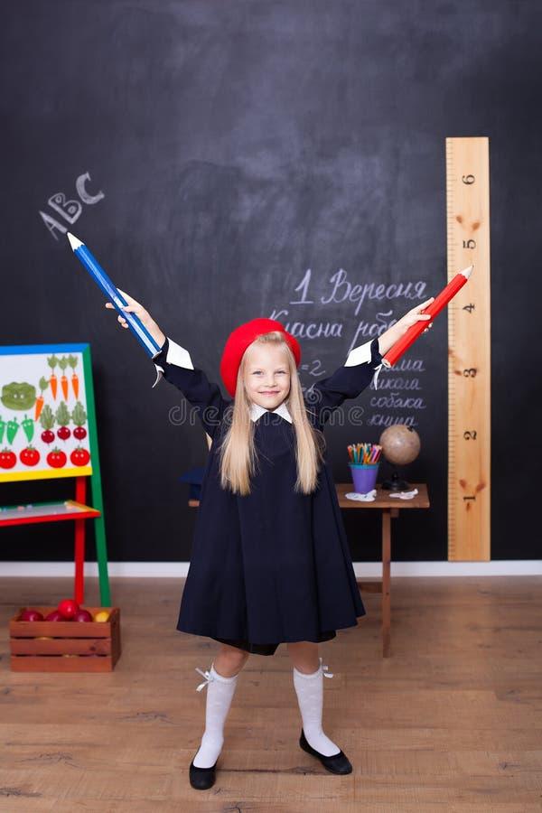 Πίσω στο σχολείο! Ένα μικρό κορίτσι στέκεται με τα μεγάλα μολύβια στα χέρια της στο σχολείο Το σχολικό κορίτσι αποκρίνεται στο μά στοκ φωτογραφίες με δικαίωμα ελεύθερης χρήσης