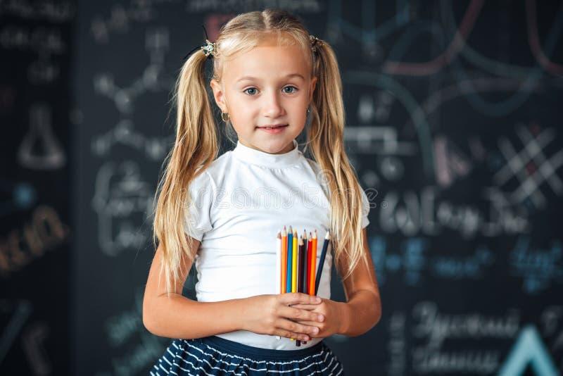 Πίσω στο σχολείο! Ένα μικρό κορίτσι στέκεται με τα μολύβια στα χέρια της ενάντια στον πίνακα κιμωλίας με τους σχολικούς τύπους στ στοκ εικόνες με δικαίωμα ελεύθερης χρήσης