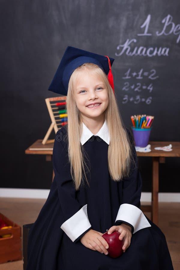 Πίσω στο σχολείο! Εύθυμο μικρό κορίτσι στο σχολείο σε ένα μαύρο υπόβαθρο Να εξετάσει τη κάμερα Σχολική έννοια Μαθήτρια στην κατηγ στοκ φωτογραφία