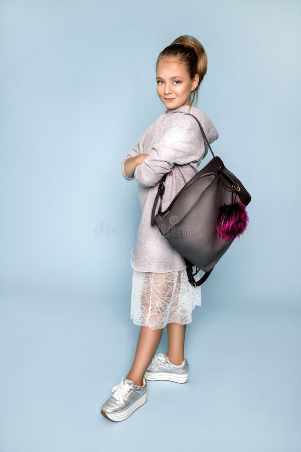 Πίσω στο σχολείο και τον ευτυχή χρόνο! Το χαριτωμένο εργατικό παιδί σπάζει μέσω του τοίχου εγγράφου χρώματος Παιδί με το σακίδιο  στοκ εικόνες