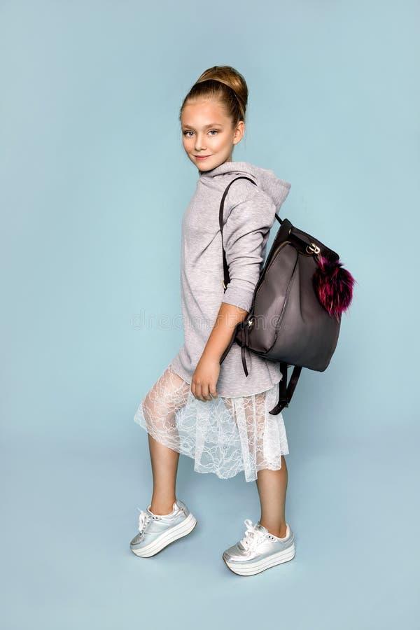 Πίσω στο σχολείο και τον ευτυχή χρόνο! Το χαριτωμένο εργατικό παιδί σπάζει μέσω του τοίχου εγγράφου χρώματος Παιδί με το σακίδιο  στοκ φωτογραφίες