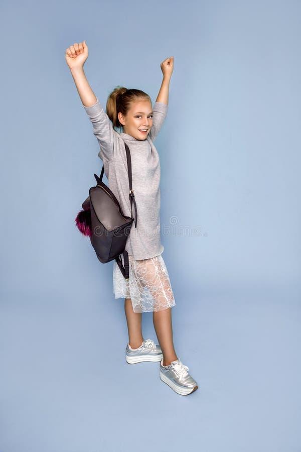 Πίσω στο σχολείο και τον ευτυχή χρόνο! Το χαριτωμένο εργατικό παιδί σπάζει μέσω του τοίχου εγγράφου χρώματος Παιδί με το σακίδιο  στοκ εικόνες με δικαίωμα ελεύθερης χρήσης