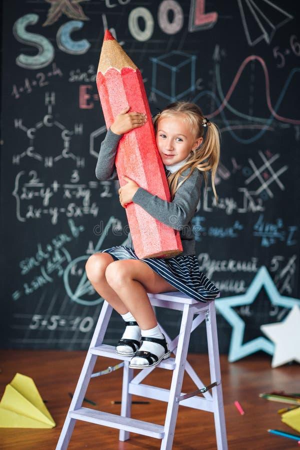 Πίσω στο σχολείο! Το λίγο ευτυχές ξανθό κορίτσι στη σχολική στολή κάθεται με το πολύ μεγάλο κόκκινο μολύβι στα χέρια της στο σχολ στοκ εικόνες με δικαίωμα ελεύθερης χρήσης
