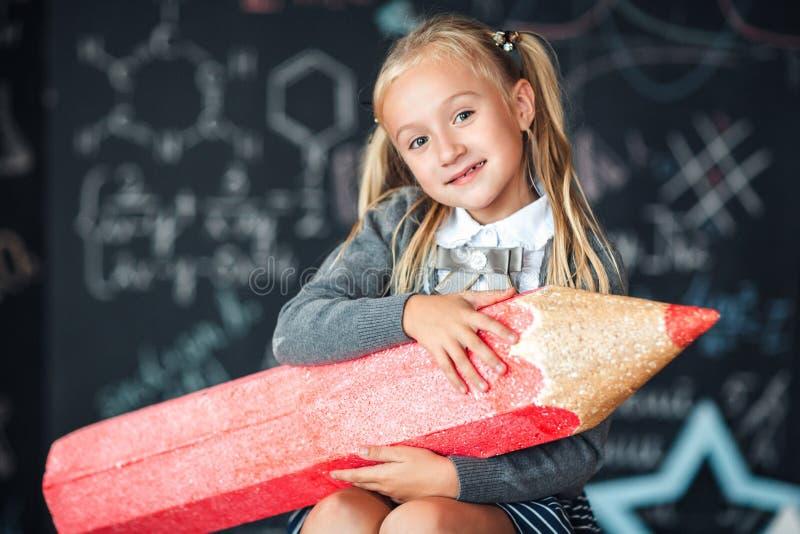 Πίσω στο σχολείο! Το λίγο ευτυχές ξανθό κορίτσι στη σχολική στολή κάθεται με το πολύ μεγάλο κόκκινο μολύβι στα χέρια της στο σχολ στοκ εικόνες