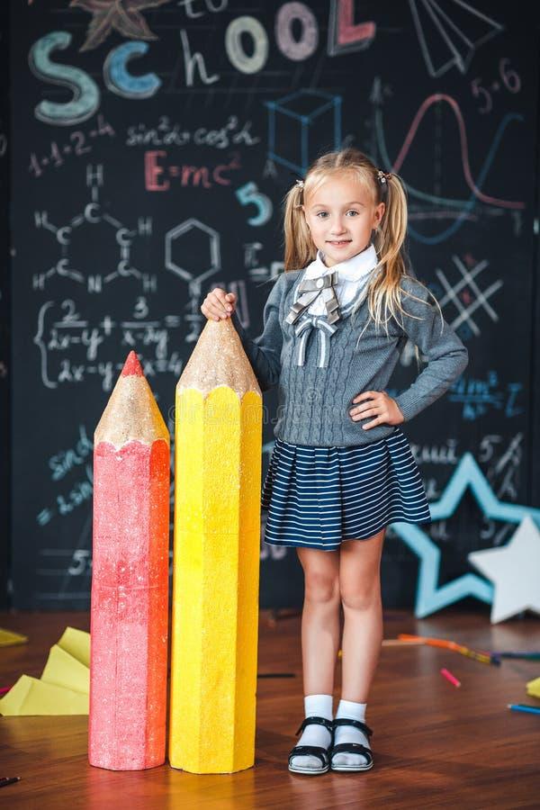Πίσω στο σχολείο! Το λίγο ξανθό κορίτσι στη σχολική στολή στέκεται με δύο πολύ μεγάλα μολύβια στο floore ενάντια στον πίνακα κιμω στοκ εικόνες με δικαίωμα ελεύθερης χρήσης
