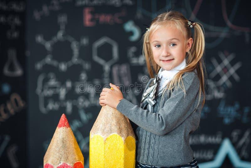 Πίσω στο σχολείο! Το λίγο ξανθό κορίτσι στη σχολική στολή στέκεται με δύο πολύ μεγάλα μολύβια στο floore ενάντια στον πίνακα κιμω στοκ φωτογραφία με δικαίωμα ελεύθερης χρήσης