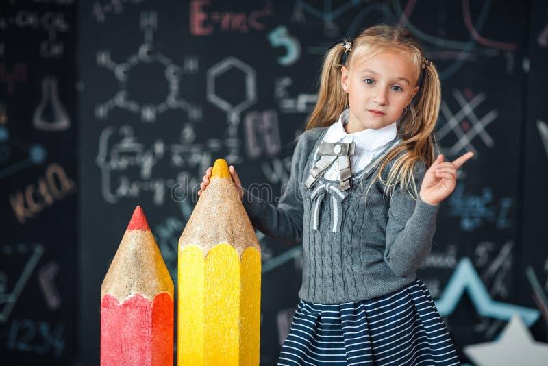 Πίσω στο σχολείο! Το λίγο ξανθό κορίτσι στη σχολική στολή στέκεται με δύο πολύ μεγάλα κόκκινα και κίτρινα μολύβια στο floore ενάν στοκ φωτογραφία με δικαίωμα ελεύθερης χρήσης