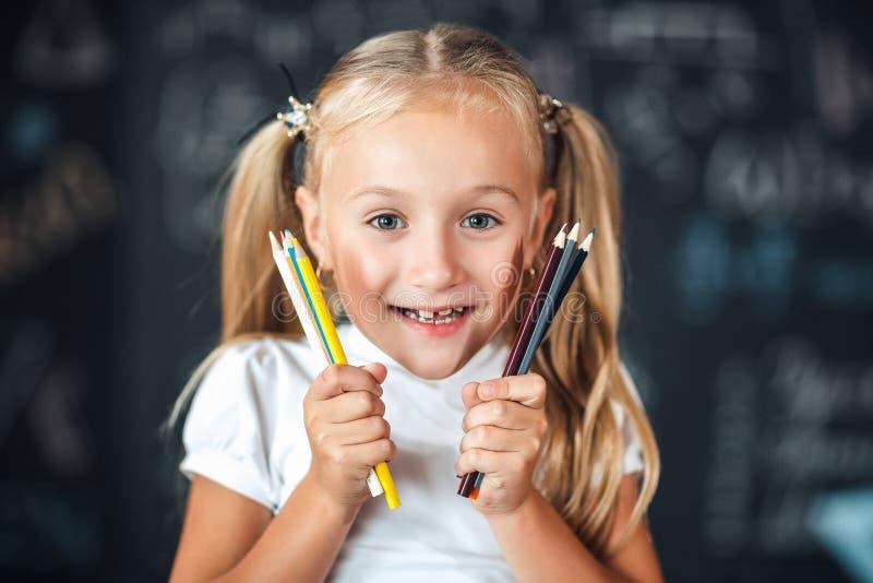 Πίσω στο σχολείο! Το πορτρέτο χαμογελά λίγο τις στάσεις κοριτσιών με την εκμετάλλευση κοριτσιών χρωμάτισε τα μολύβια κοντά στο πρ στοκ εικόνες με δικαίωμα ελεύθερης χρήσης