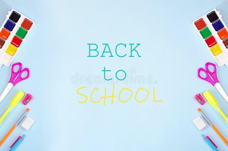 Πίσω στο σχολικό έμβλημα με τα χαρτικά και το μπλε υπόβαθρο στοκ φωτογραφία με δικαίωμα ελεύθερης χρήσης